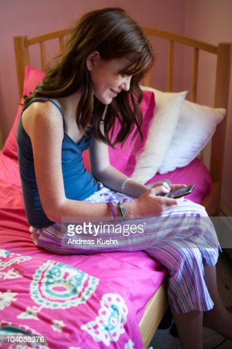 13 year old teenage girl texting in her bedroom stock