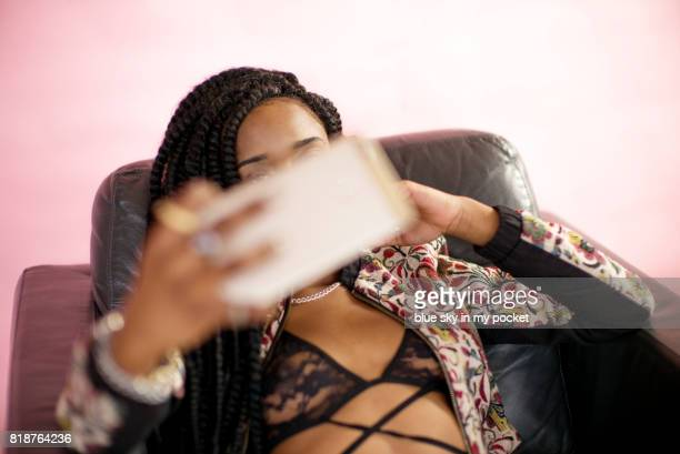 a 19 year old teenage girl using her phone. - erin james stock-fotos und bilder