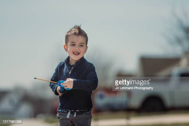 3 1/2 year old toddler plays with toys outside during quarantine alone - remote controlled car stock pictures, royalty-free photos & images