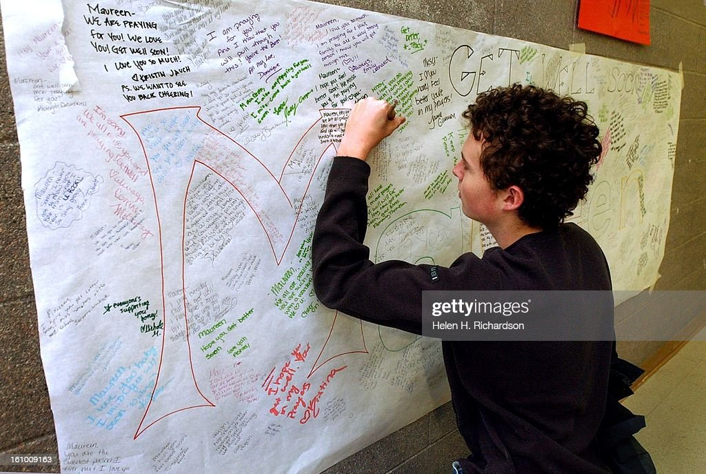 16 year old Tyler Thome signs a large Get Well Card for Maureen Martin at Douglas County High School. Since the kids have been asked not to go to the hospital, kids at the school wanted to give Martin something to help her through her injuries she suffere : News Photo
