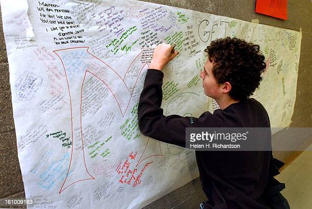 16 year old Tyler Thome signs a large Get Well Card for Maureen Martin at Douglas County High School Since the kids have been asked not to go to the...