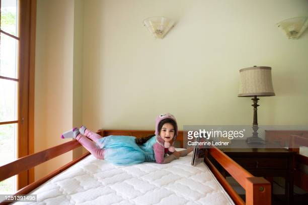 3 year old wearing costume and hat reading book propped up in unmade bed - catherine ledner stock pictures, royalty-free photos & images
