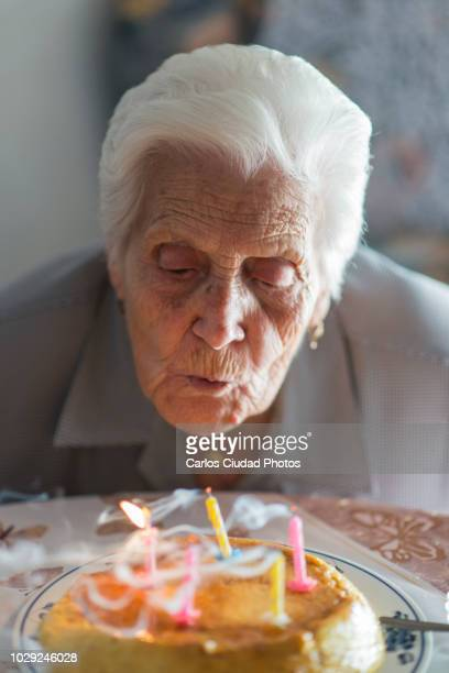 95 year old woman blowing out birthday candles at home - 90 plus years stock pictures, royalty-free photos & images