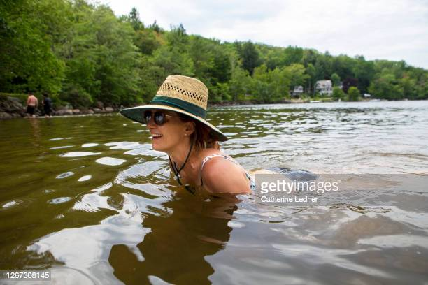 40 year old woman cooling off in lake water in maine, wearing a wide brimmed hat and sun glasses - catherine ledner stock pictures, royalty-free photos & images