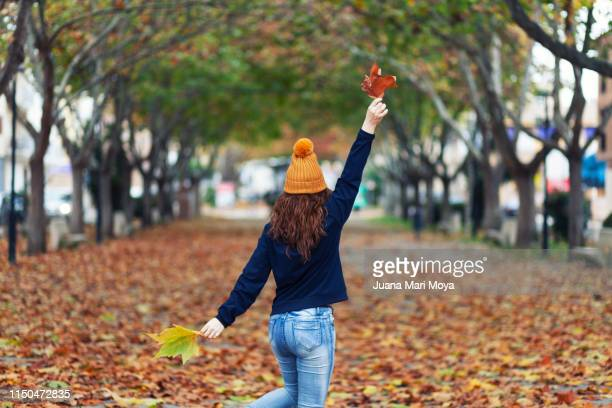 45 year old woman dancing on autumn leaves - 45 49 anni foto e immagini stock