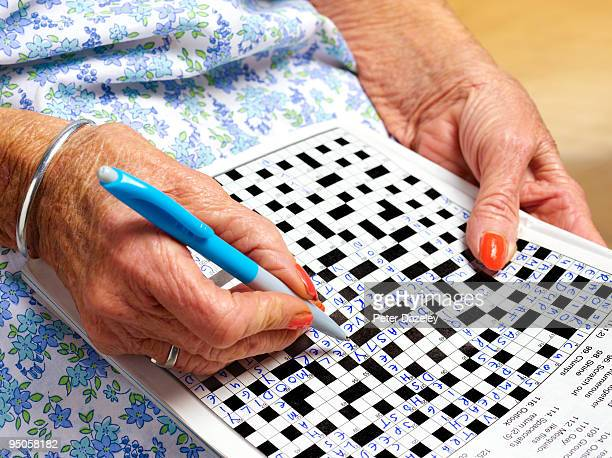 70 year old woman doing crossword puzzle