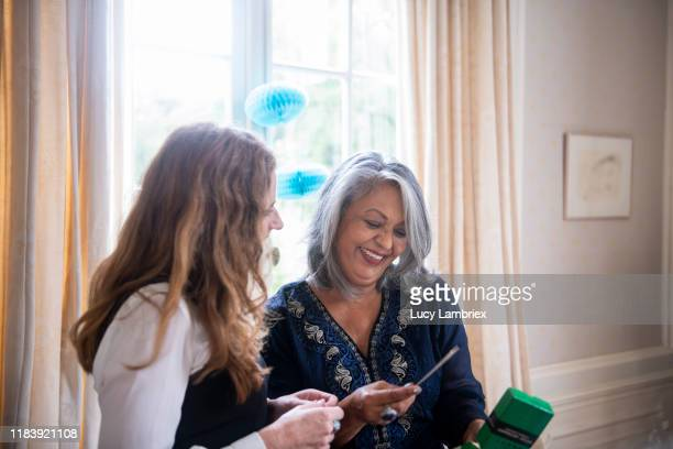 65 year old woman enjoying her present at her birthday - giving stock pictures, royalty-free photos & images
