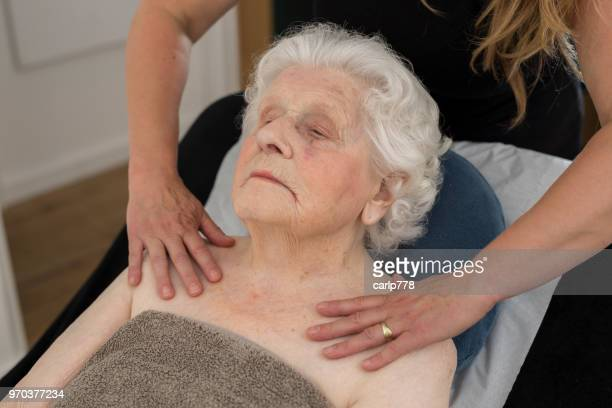 100 year old woman getting a shoulder massage
