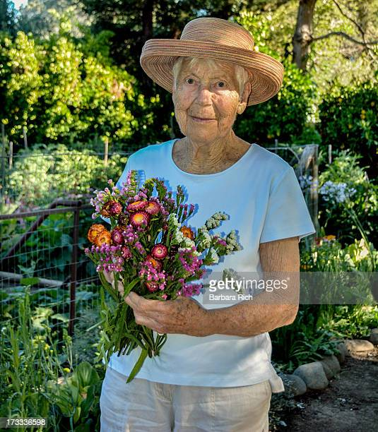 92 year old woman hodling bouquet in the garden
