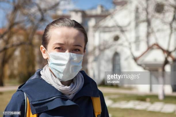 donna di 35 anni in maschera n95 vicino alla chiesa cattolica - cattolicesimo foto e immagini stock