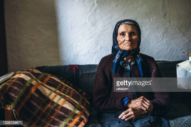 90 year old woman sitting on bed - 90 plus years stock pictures, royalty-free photos & images