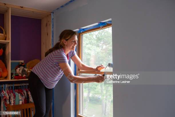 40 year old woman smiling while painting edge of wall with paint roller. - catherine ledner stock pictures, royalty-free photos & images