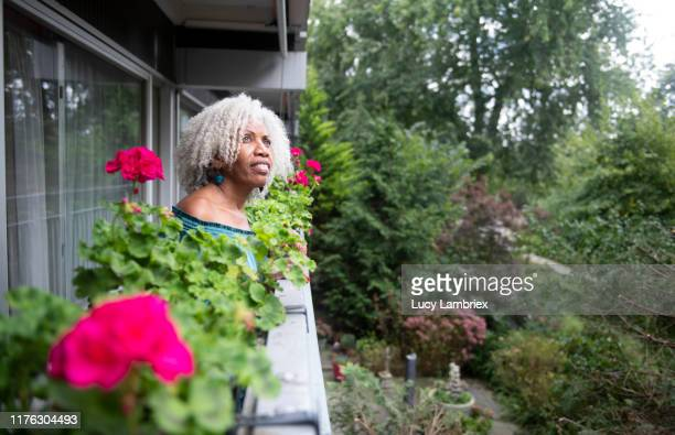 62 year old woman standing on the balcony, looking at the surroundings - 63 year old female stock pictures, royalty-free photos & images