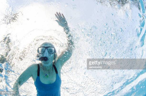 67 year old woman swimming underwater with mask