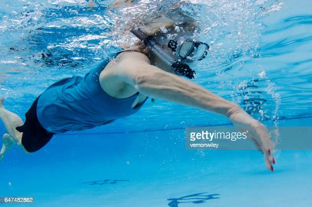 67 year old woman swimming underwater with snorkel
