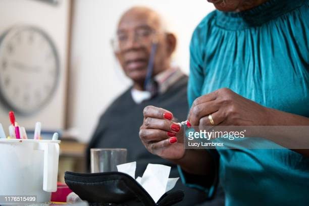 62 year old woman with a tool for measuring her 91 year old father's blood sugar level: attaching / detaching the needle - 63 year old female stock pictures, royalty-free photos & images