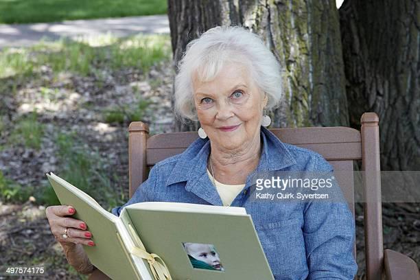 84 year old woman with photo album - kathy self fotografías e imágenes de stock