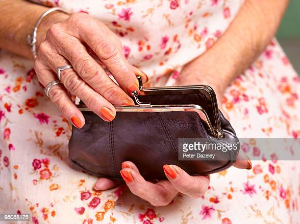 70 year old woman's hands opening purse