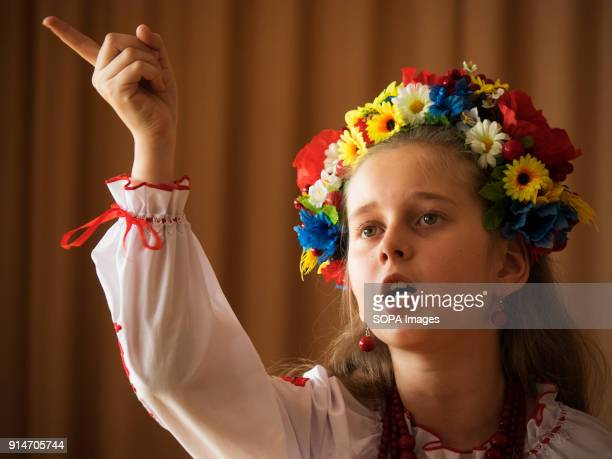 A 10 year old young girl dress in the embroidered traditional Ukrainian ornament shirt and flower wreath reads poetry in a local school