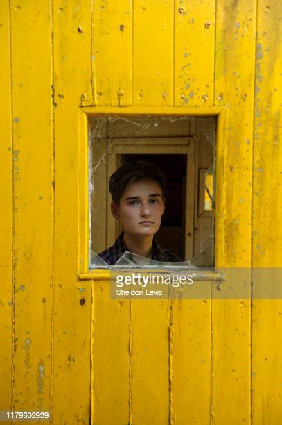 16 year old young woman gazing through broken window in bright yellow wooden wall - by sheldon levis fotografías e imágenes de stock