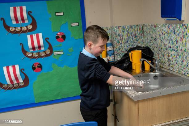 Year six pupil washes his hands after returning to the classroom from an outdoor break period at Willowpark Primary Academy in Oldham, northern...