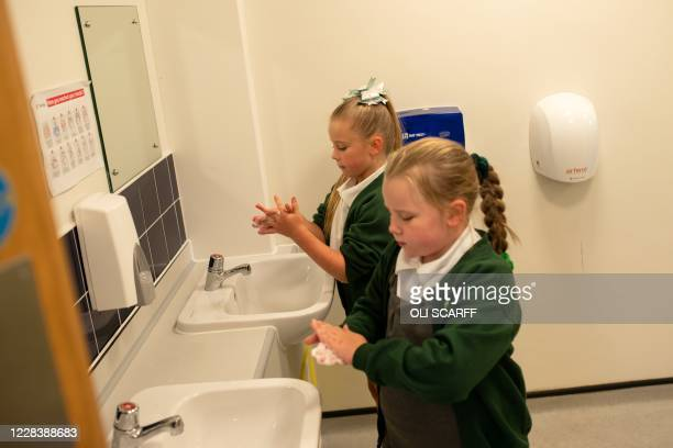 Year three pupils wash their hands after returning from outside play at Woodlands Primary Academy in Oldham, northern England on September 7, 2020. -...
