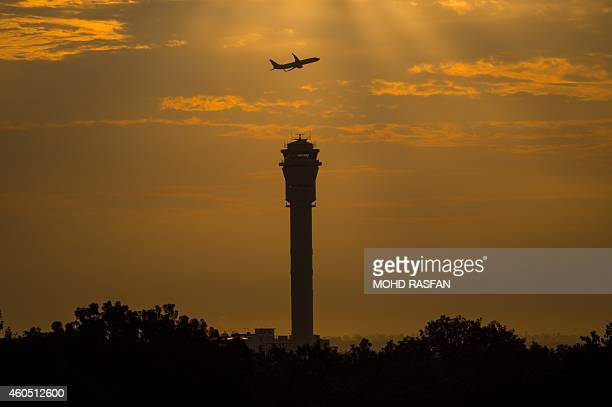 Year2014aviationaccidentsafetyFOCUS BY Dan Martin This photo taken on December 11 shows an airplane flying past a control tower at Kuala Lumpur...