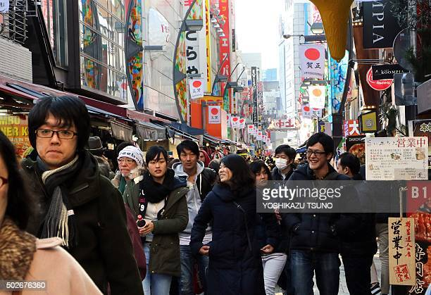 Yearend shoppers crowd a narrow street in the Ameyoko shopping district in Tokyo on December 28 2015 More than one million people are expected to...