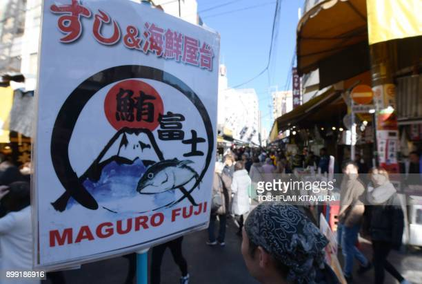 Yearend shoppers visit shops selling fresh and dried seafood outside Tsukiji fish market in Tokyo on December 28 2017 People visited the shops to...