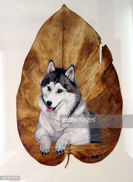 'Yearning' work of art where a dog is painted on one leaf by artist Pang Yande is seen during 'Cherish Nature Pang Yande Leaves Painting Art Show'at...