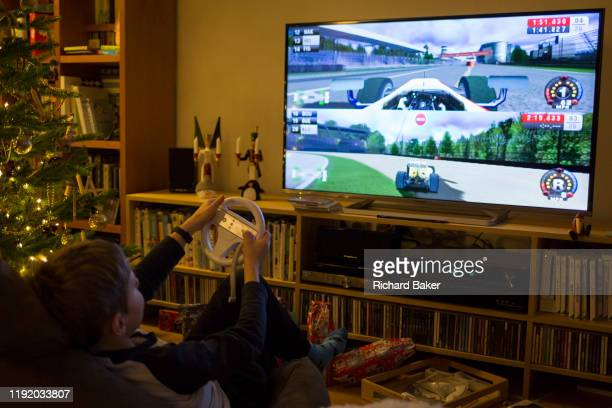 A 10 yearold boy plays Formula 1 Wii on a widescreen TV on Christmas Day on 25th December 2019 in Bristol England