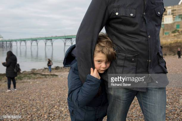 A 9 yearold boy plays with his dad on the beach at Clevedon Pier on 27th December 2018 in Clevedon North Somerset UK