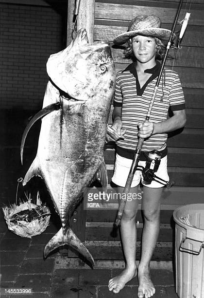 A 14 yearold boy stands next to a 62 pound giant trevally he caught circa 1970