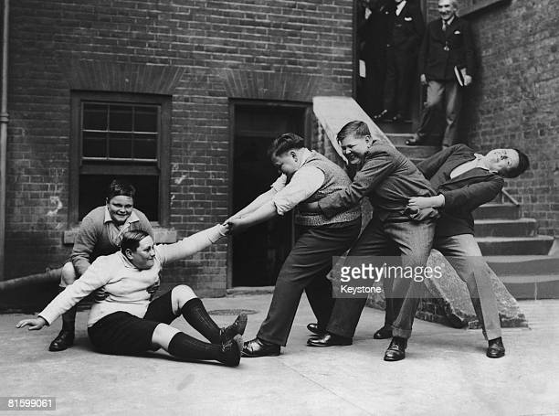 A 13 yearold boy who weighs 14 stone is helped to his feet by his companions 3rd June 1931 They are part of a group of fat boys being entertained to...