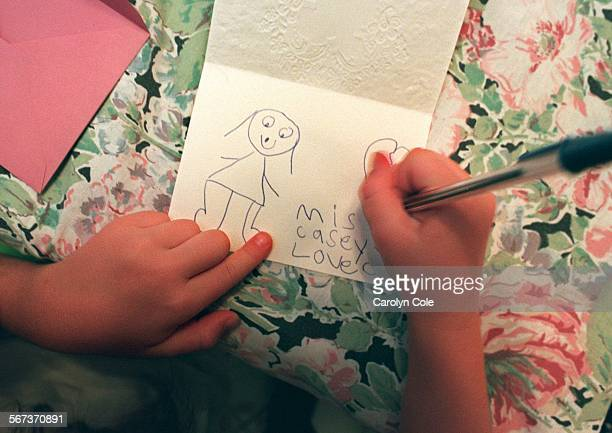 6–year–old Casey Kelly writes a thankyou note including a picture to one of her 5 teachers who she and her mother Kimberly Kelly are giving gifts to...