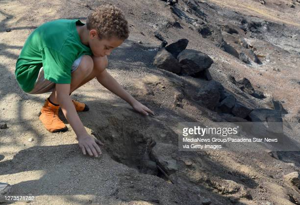 8 yearold CJ Kenton buries a rabbit that had died in the fire in front of burned out structures of his grandfather Frank Kenton during the Bobcat...