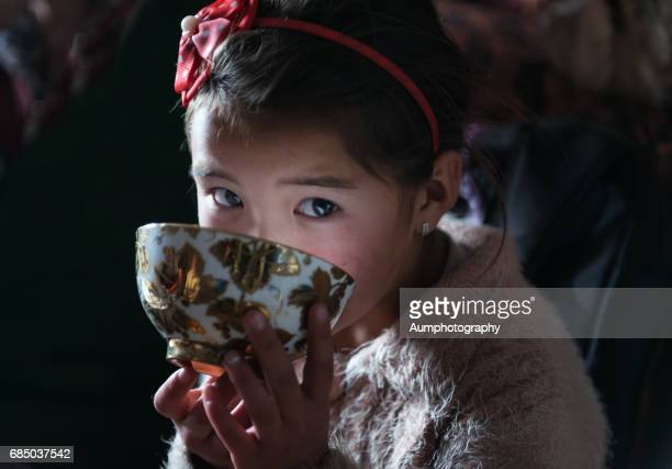 6 year-old eagle huntress relaxing tea times in mongolia. - mongolian women stock photos and pictures