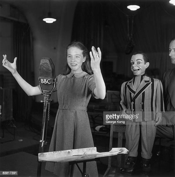 14 yearold English actress Julie Andrews with ventriloquist Peter Brough and his dummy Archie Andrews on the BBC radio show 'Educating Archie' 10th...