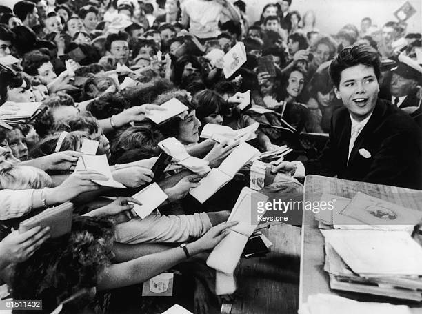 18 yearold English pop singer Cliff Richard is mobbed by fans at the Hulton Boys and Girls Exhibition at Olympia's Disc Theatre 19th August 1959