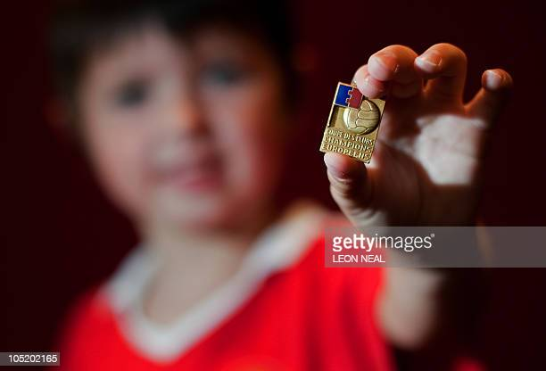 6 yearold Harvey Darwick poses for the photogrpaher with a 1968 European Cup Final medal that was previously owned by footballer George Best at...