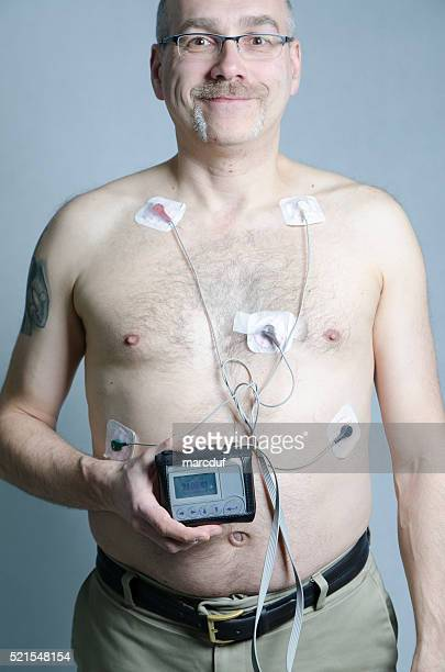 50 year-old man with 5 sensors with holter monitor - holter monitor stock photos and pictures