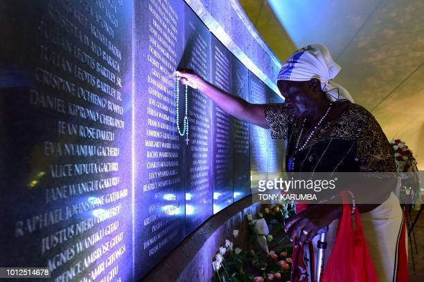80 yearold Margaret Achieng holds her rosary to the name of her daughter Doreen on the plaque bearing the names of those killed in the 1998 bombing...