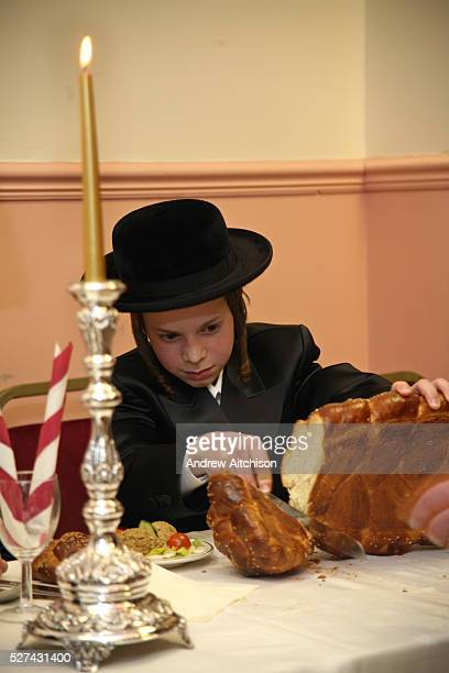 Year-old Orthodox Jewish boy cuts the bread for everyone at his Bar Mitzvah meal. The Bar Mitzvah signals the coming of age for a young Jewish boy,...