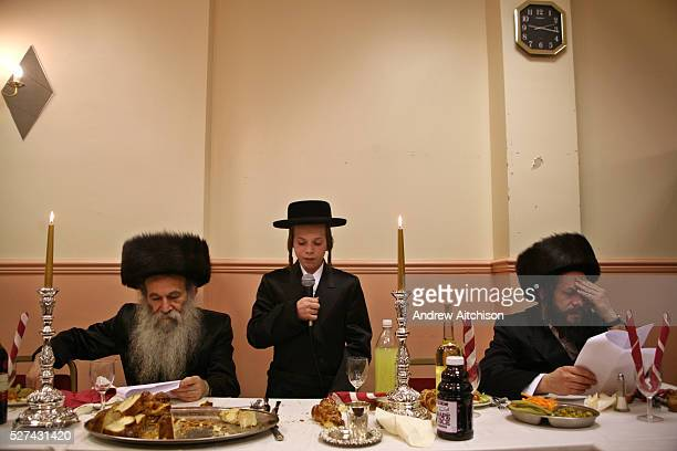A 13 yearold Orthodox Jewish boy recites the Torah during Bar Mitzvah His father and grandfather listen closely to make sure he doesn't make any...