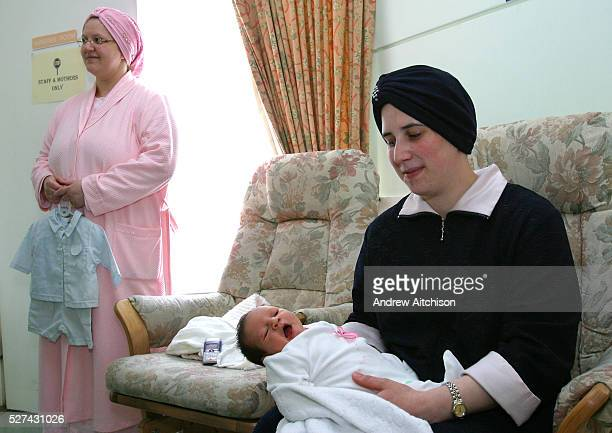 A 28 yearold Orthodox Jewish mother shows off her 3 dayold baby After having her child she is staying in Beis Brucha a mother and baby home run by...