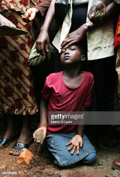8 yearold Ruth Nakabonge throws earth over her fathers coffic during his funeral on December 14 2005 in Bbambula a village 50 km North of the capital...