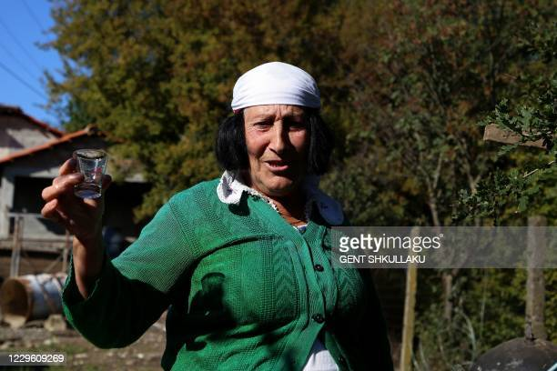 Year-old Vitore Vas Lufi makes homemade raki, a traditional spirit, using an old still in the yard of her home in the village of Fishta, northern...