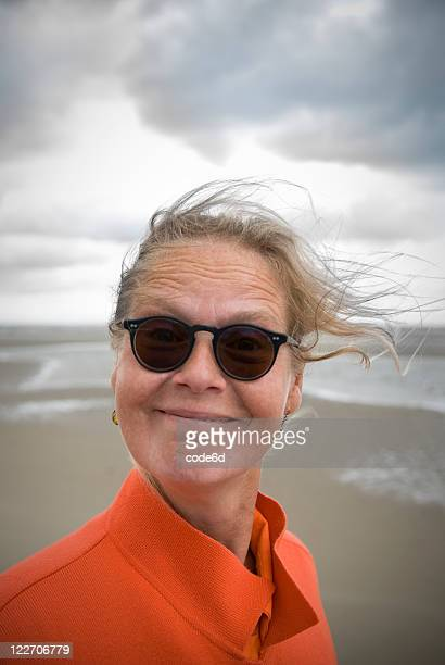 50 year-old woman at beach, sunglasses, smiling happily, copy space