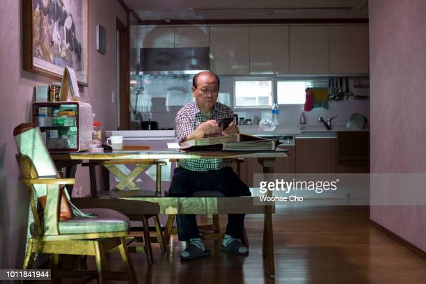 81 yearold Yoon Ilyoung sits in front of the pictures of himself taken in North Korea 70 years ago in his appartment in Seoul South Korea on July 12...