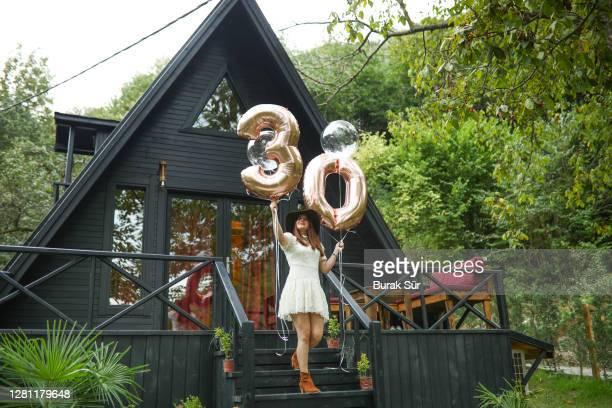 30 jahre geburtstagsparty und schöne frau vor dem bungalowhaus - 30 34 years stock-fotos und bilder